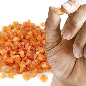 Clickerfutter soft im Hintergrund und eine Hand die ein Stückchen hält um die Größe zu zeigen